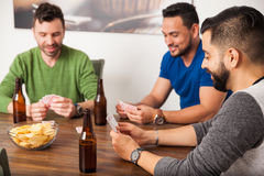 Friends playing cards and hanging out. Group of three friends having some fun playing cards and drinking beer at home stock image