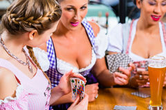 Friends playing cards in Inn or pub drinking beer royalty free stock photo