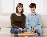 Friends playing chess in livingroom Stock Photos