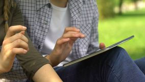 Friends playing computer game on tablet in park, leisure time with mobile app. Stock footage stock footage