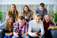 Friends playing a console game Royalty Free Stock Image