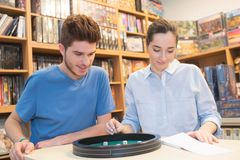 Friends playing dice at game shop Royalty Free Stock Images