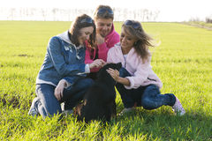 Friends playing with a dog Royalty Free Stock Photo
