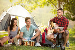 Friends playing drums and guitar front tent Stock Images