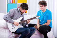 Friends playing electric guitar Royalty Free Stock Image