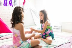 Friends Playing Fist Stacking Game At Sleepover Party. Best friends playing fist stacking game while sitting on duvets at sleepover party stock photo