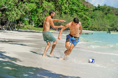 Friends playing footbal at the sunny tropical beach.  Stock Photos