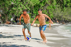 Friends playing footbal at the sunny tropical beach.  Royalty Free Stock Photo