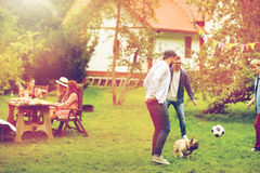 Friends playing football with dog at summer garden Royalty Free Stock Image