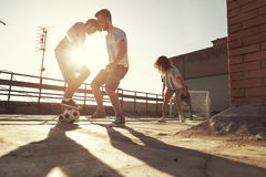 Friends playing football. Group of young friends having fun playing football on a building rooftop royalty free stock photography