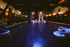 Friends playing a game of air hockey Royalty Free Stock Images