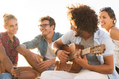 Friends playing guitar Royalty Free Stock Image