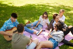 Friends playing guitar at picnic in summer park stock photography