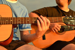 Friends playing guitar. At the seacoast Stock Images