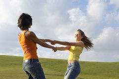 Friends Playing While Holding Hands Against Cloudy Sky Royalty Free Stock Photos