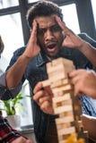 Friends playing jenga game Stock Photo
