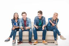 Friends playing with joysticks. Happy young friends playing with joysticks and drinking from soda cans  on white Royalty Free Stock Photography