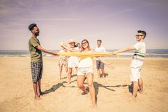 Friends playing at limbo. Group of happy and playful friends playing at limbo on the beach - Tourists on vacation on a tropical travel destination on summertime Royalty Free Stock Image