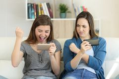 Friends playing on line and one winning. Friends playing on line games with smartphones and one winning sitting on a couch in the living room at home Stock Images