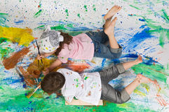 Friends playing with painting. On the background painted Royalty Free Stock Photography