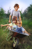 friends playing in the plane using a garden carts Royalty Free Stock Photo