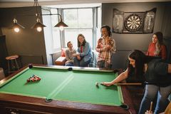Friends Playing Pool. Small group of friends playing pool in a games room in a house stock photo