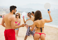 Friends playing with rackets at beach Stock Photo