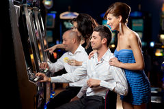 Friends playing the slots Royalty Free Stock Images