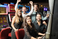 Friends playing slots in a casino. Group of five friends having a good time together while they play some slots in a casino and they win some money royalty free stock images