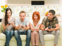 Friends playing on smartphones Royalty Free Stock Photo