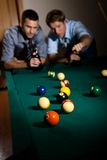 Friends playing snooker. Two young men discussing snooker game at table, having beer, focus on snooker balls Stock Image