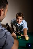 Friends playing snooker at bar. Young men looking up smiling, aiming at white ball with cue Royalty Free Stock Photo