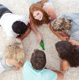 Friends playing spin the bottle on the floor Royalty Free Stock Image