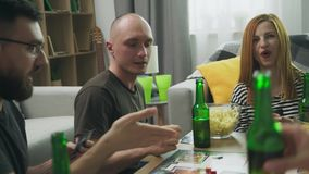 Friends playing in strategic board game with cards and dice in cozy living room.  stock video