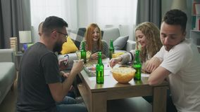 Friends playing in strategic Board Game with cards and dice in cozy living room.  stock video footage
