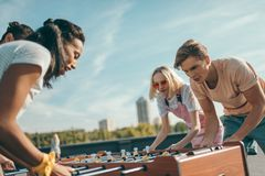 Friends playing table football. Group of young friends playing table football on roof Stock Image