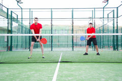 Friends playing team  paddle tennis. Royalty Free Stock Photography