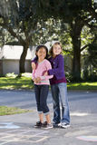 Friends playing together on driveway. Two girls at home on driveway standing in front of hopscotch board (7 years Royalty Free Stock Photography