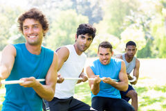 Friends playing tug of war in park Stock Photo