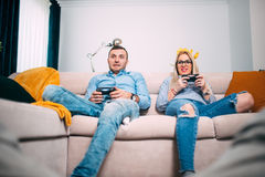 Friends playing video games with joystick Controllers. Young people having fun with modern technology and playing on console Royalty Free Stock Photo