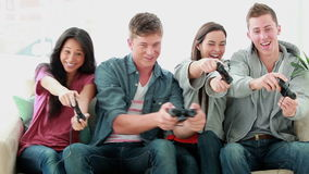 Friends playing video games while laughing Royalty Free Stock Photos
