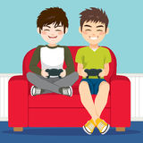 Friends Playing Video Games. Friends together sitting on couch playing video games Royalty Free Stock Photo