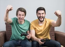 Friends playing video games. Two young friends playing awesome video games sitting on sofa and holding gamepads. Tourney or tournament concept Royalty Free Stock Photography