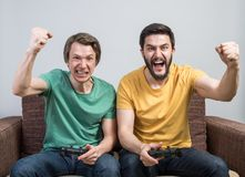 Friends playing video games. Two young friends playing awesome video games sitting on sofa and holding gamepads. Tourney or tournament concept Royalty Free Stock Photo