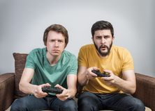Friends playing video games. Two young friends playing awesome video games sitting on sofa and holding gamepads. Tourney or tournament concept Stock Photos