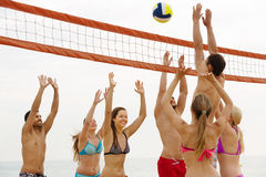 Friends playing volleyball at beach Royalty Free Stock Image