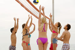 Friends playing volleyball at beach Stock Photos