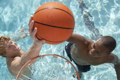 Friends Playing Water Basketball In Pool Royalty Free Stock Image