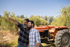 Friends pointing at distance in farm. On a sunny day Stock Photos