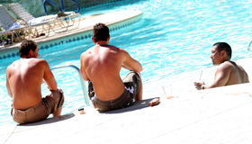 Friends at the pool. Three male friends sitting at the pool Stock Images